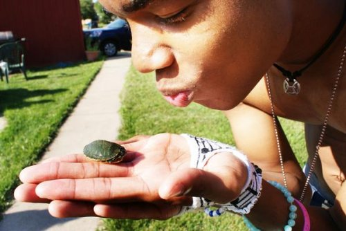 Medium-skinned person wearing several bracelets and two necklaces, sitting outside and holding a very small turtle in the palm of their hand, pursing their lips as if about to kiss the turtle.