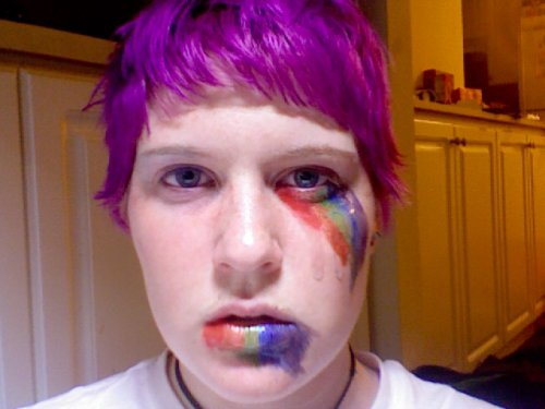 Androgynous white person wearing smudged rainbow lipstick and equally smudged rainbow facepaint going down from one eye. They have short purple hair and blue eyes.
