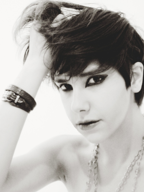 Androgynous pale-skinned person with short brown hair, wearing dramatic eyeliner and lipstick, a chain necklace, and a few leather-appearing bracelets. They are running one hand through their hair and looking intensely at the camera.