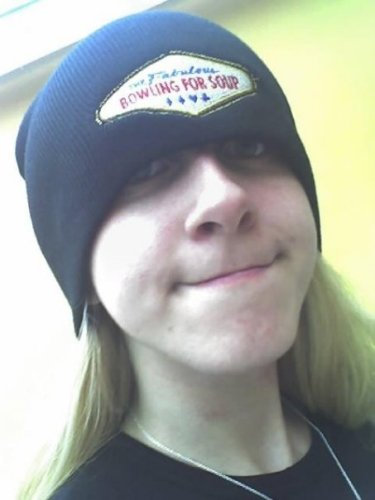 Pale-skinned person with long dirty blonde hair, wearing a toque that says Bowling For Soup on the front which is pulled down over their eyes. They are giving a tight-lipped smile to the camera.