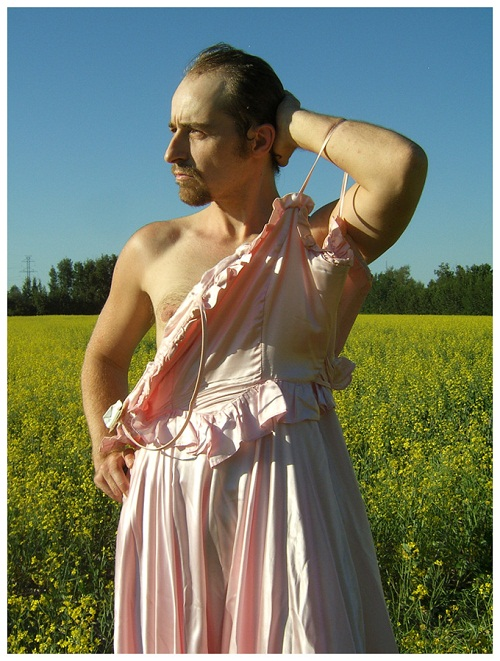 A trans man with a goatee stands in a grassy field wearing an undone, pale pink dress and looking off to the side.