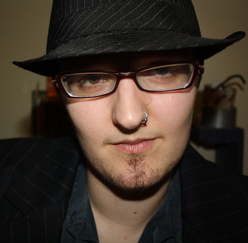 Headshot of a person with a nose ring and a faint goatee, wearing a black pinstripe suit with a matching fedora and rectangular glasses, smirking slightly at the camera.