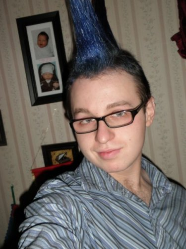 Pale-skinned person wearing black rectangle-framed glasses and a grey striped button-down, with their hair spiked into an exceptionally long blue mohawk. They are looking at the camera and smiling slightly.