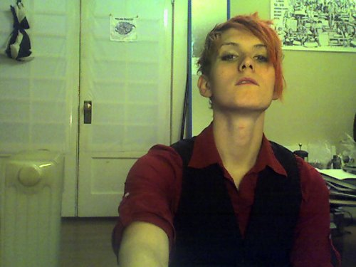 Woman with pale skin wearing a red button down shirt and a black vest. Her hair is cut short and uneven, dyed red. She is looking at the camera with her chin tilted up.