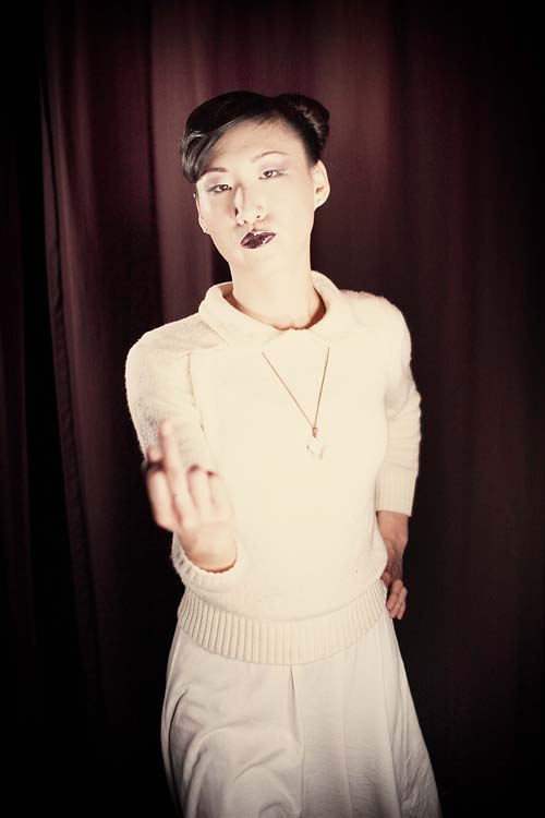 Asian person with shiny black hair tied back, wearing dark lipstick and a pink collared sweater with a skirt, one hand on their hip and the other held out with a raised middle finger.