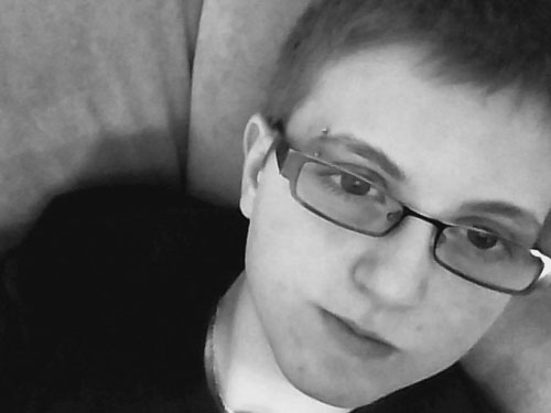 An androgynous light-skinned person with an eyebrow piercing, short hair and rectangular glasses, resting against some cushions and gazing slightly past the camera with a thoughtful expression.