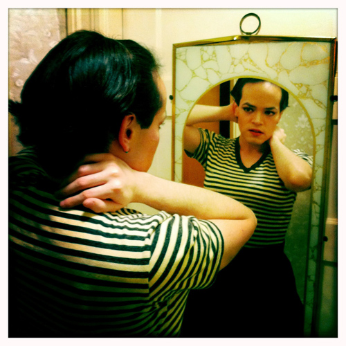 Person with short dark hair, wearing red lipstick, a striped shirt and a dark-coloured skirt, looking into a mirror as though getting ready to go out.