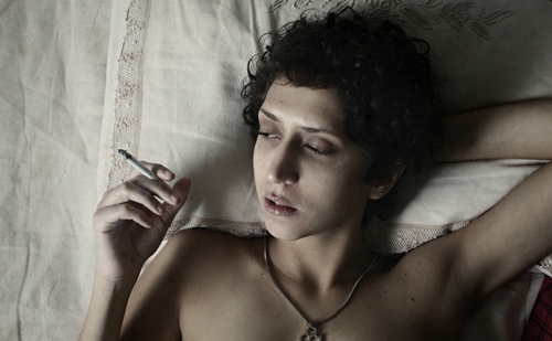 Light-skinned person with short curly hair, apparently shirtless, lying on a bed with their head resting on one hand and a cigarette in the other, looking off-screen.