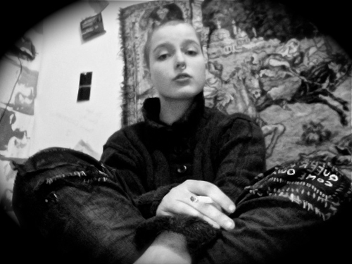 White person with a shaved head and pierced septum, wearing baggy jeans and a sweater, sitting cross-legged in front of a medieval-style tapestry, holding a cigarette and looking down at the camera.