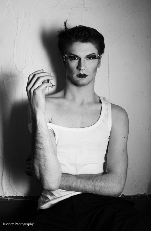 Black-and-white photo of a pale-skinned person with short dark hair and hairy arms, wearing a white sleeveless shirt with one strap fallen down off their shoulder. They have heavy eye makeup and lipstick on, and fake eyelashes. They are holding a cigarette and looking at the camera.