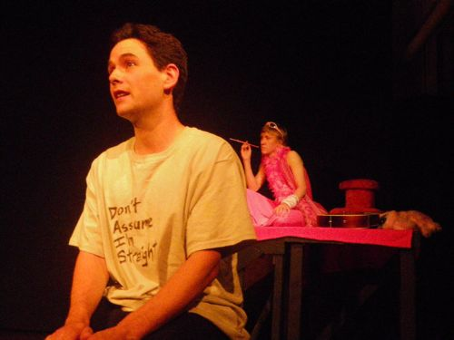 "A person sitting on a stage, wearing a t-shirt reading ""Don't Assume I'm Straight"". Behind them is another person clad completely in pink, smoking a cigarette in a long holder."