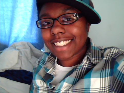 Dark-skinned person smiling, wearing glasses, a cap tilted at an angle, and a plaid shirt.