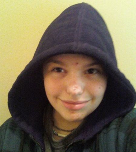 A person wearing a hoodie and smiling at the camera.