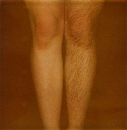 Yellow-tinted polaroid photo of a person's legs, one of which is shaved smooth and the other of which is hairy.