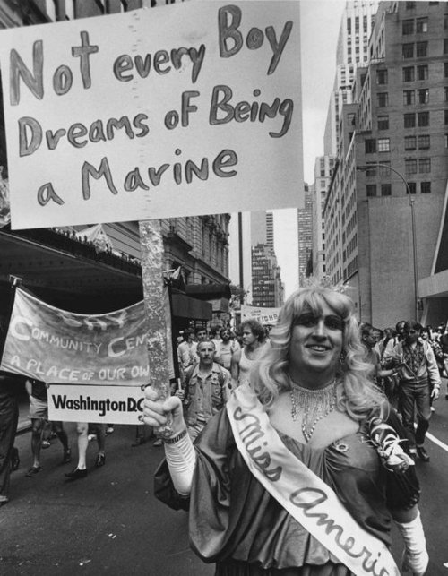 "Male-assigned person wearing a blonde wig and an evening gown, with a sash saying ""Miss America"", walking in a Pride parade and holding up a sign which reads, ""Not every boy dreams of being a marine."""