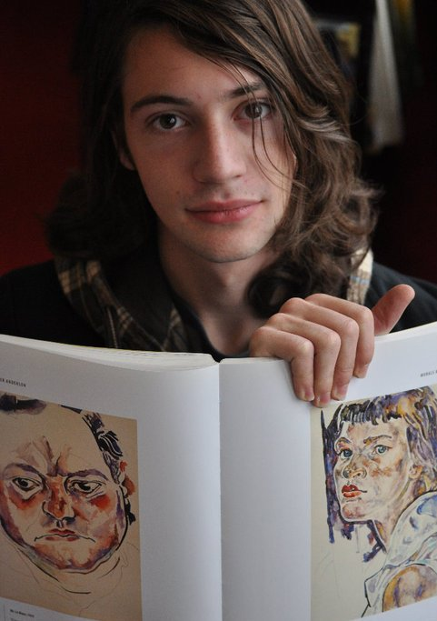 Androgynous light-skinned person with medium-length brown curly hair. They are smiling at the camera and holding up a book of paintings.