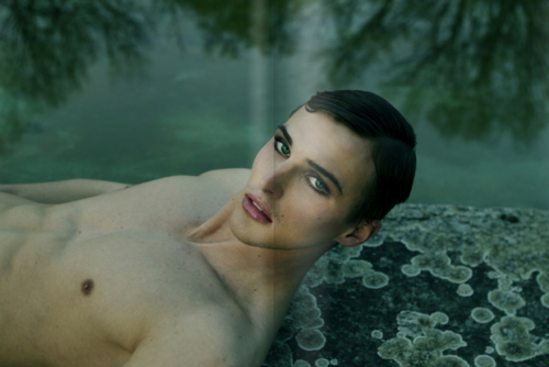 Pale-skinned person with neatly combed short dark hair, shirtless, lying outside on a stone by a river, looking at the camera. They are wearing dramatic eyeliner and lipstick, and their eyebrows are shaped.