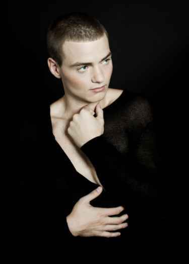 Pale-skinned man with a dark buzzcut wearing a thin, translucent black cardigan, pulling it over his chest in a typically feminine manner while looking off to the side.