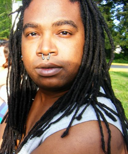 Dark-skinned person with long dreadlocks and a nose piercing, standing outside in the sun.