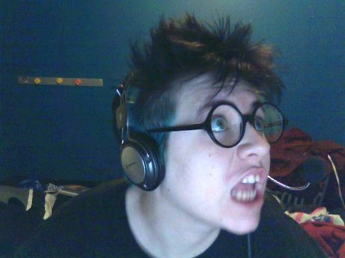 Person with messy hair wearing headphones and round glasses making a face at something offscreen.