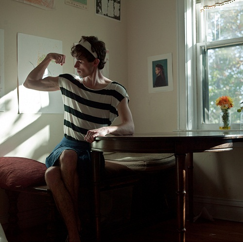 Person with curly hair sitting on a bed wearing a skirt and a striped shirt, flexing rather sizable biceps.