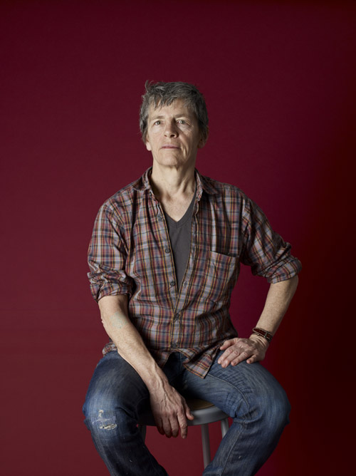 Older light-skinned butch woman with short grey hair, wearing jeans and a plaid shirt with the arms rolled up over a grey t-shirt. She is sitting in front of a burgundy background with one hand on her hip.