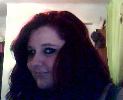 Pale person with long reddish hair, wearing eyeliner and smiling at the camera.