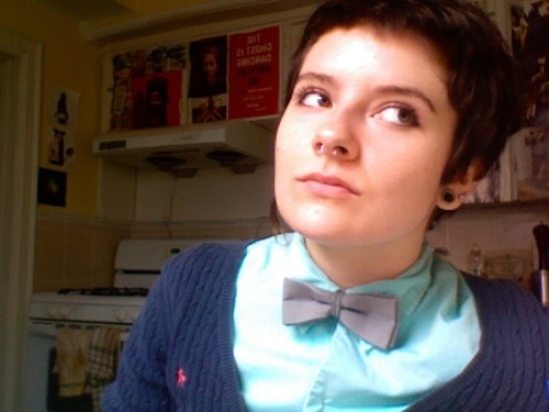Person with short hair and a pierced nose wearing a button-up pale blue shirt, a lavender bow tie, and a blue cardigan.