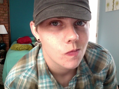 Person wearing a plaid shirt and a cap, smirking at the camera.