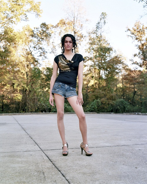 Pale person with long hair tied back, wearing high heels, short denim cut-offs, and a dark blue shirt with a gold pattern.