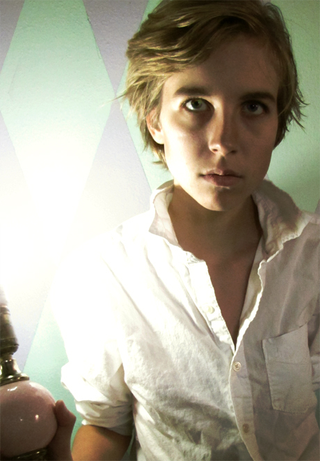 Person with blonde hair standing in a room next to a bright light, wearing a white shirt with an open collar.