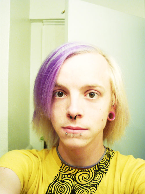 Pale blond person with a purple streak in their hair. They have facial piercings and stretched ears, and are wearing a yellow t-shirt.