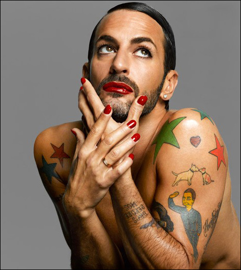 Person with facial hair and tattoos, apparently shirtless, holding their hands to their face and looking upwards. They are wearing bright red lipstick and matching nailpolish.