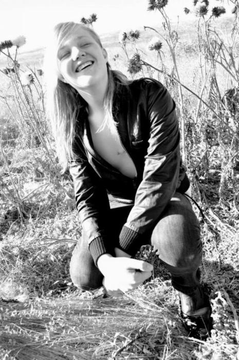 Black-and-white photo of a person with long blonde hair, wearing a leather jacket open to show their bare chest, crouching among tall thistles and smiling.