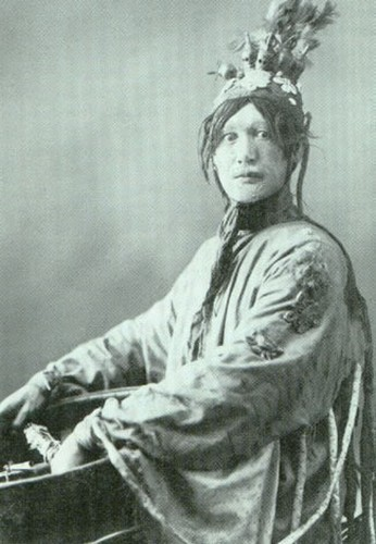 Grayscale photo of a Native person wearing a headdress, looking at the camera with wide eyes.