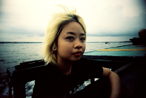 A person with dyed blonde hair, sitting in front of the ocean and looking steadily at the camera.