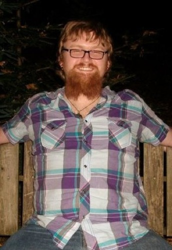A person with blond hair and a beard, wearing a purple plaid shirt and smiling broadly. Ze is sitting outside in front of a night sky.