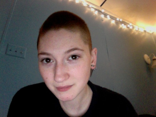 A pale person with a shaved head and two piercings in their ear, smiling at the camera.
