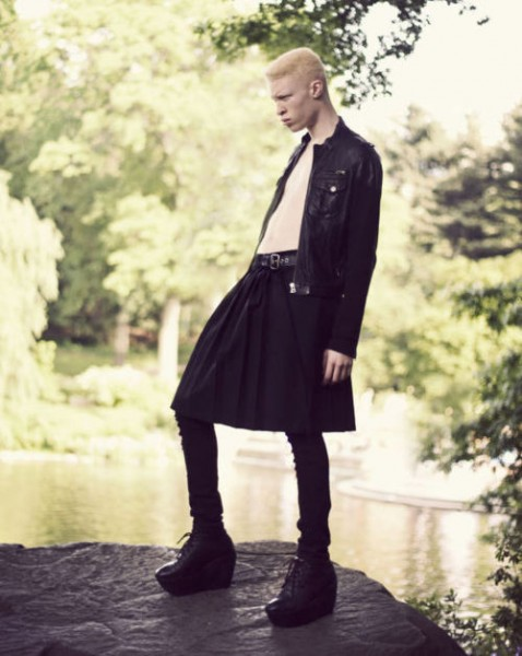 Shaun Ross, a pale person with blond hair in a buzzcut, wearing a leather jacket and a skirt over black skinny jeans and platform shoes.