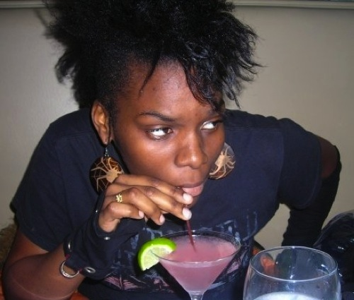 A dark-skinned person in a black t-shirt sipping a pink drink out of a martini glass and looking off to the side.