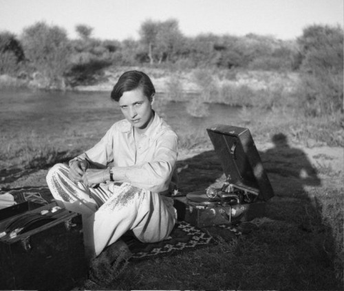 Annemarie Schwarzenbach, a person with short dark hair, wearing a white shirt and white pants, sitting at a picnic.