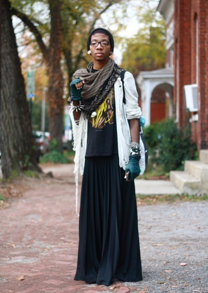 Dark-skinned person wearing glasses, earrings, a large scarf, a white sweater with the sleeves rolled up over a t-shirt, blue fingerless gloves, and a long flowing skirt. They are standing outside a few brick buildings with trees in the background.