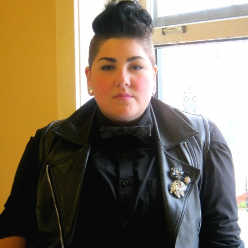 Majestic Legay, a fat light-skinned person with a mohawk in fantastic makeup, wearing a black button-down shirt and a bow tie under a black leather vest.