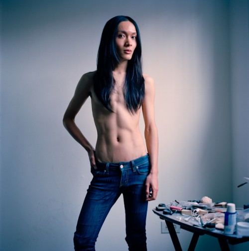 A person with long dark hair that covers their chest, standing shirtless in a room with blank white walls. Their hand is on their hip.