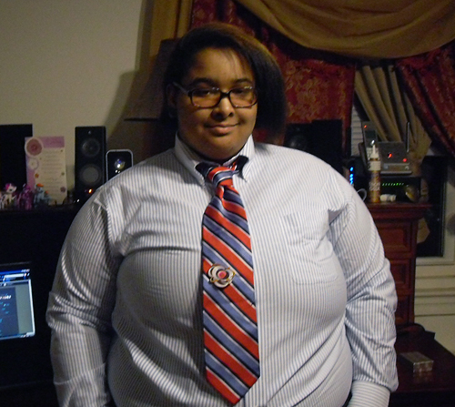 A dark-skinned person with straight hair, wearing glasses and a white shirt with a red and blue striped tie.