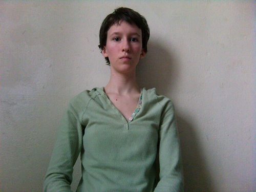 Person with short hair, wearing a seafoam-green long-sleeved shirt, standing in front of a white wall with a neutral expression.