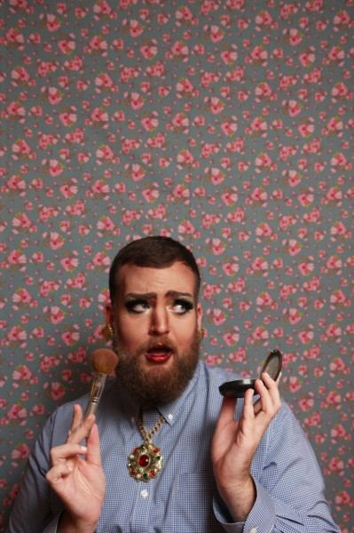A glamourous bearded person applying makeup.