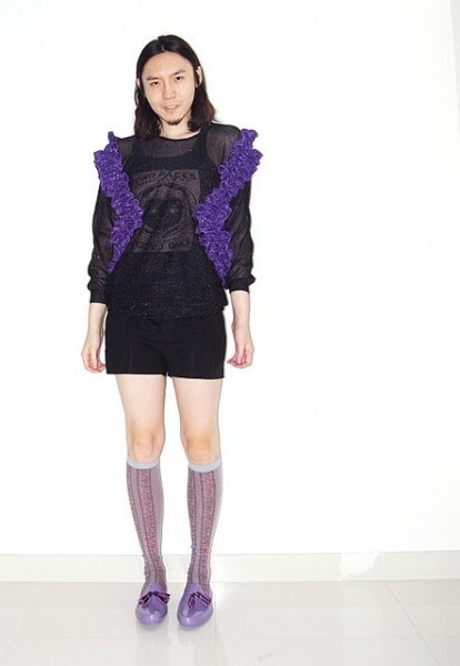 A person in shorts and a see-through top with purple frills over a tanktop. They have shoulder-length dark hair and a goatee. They are also wearing purple knee-high stockings and matching shoes.