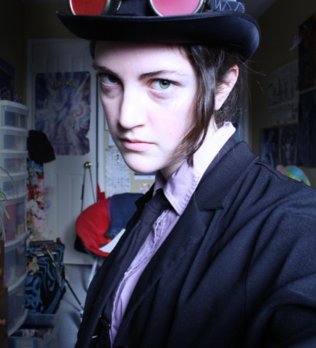 A pale person with a strand of brown hair falling over their face, wearing a top hat and a suit, staring at the camera unsmilingly.