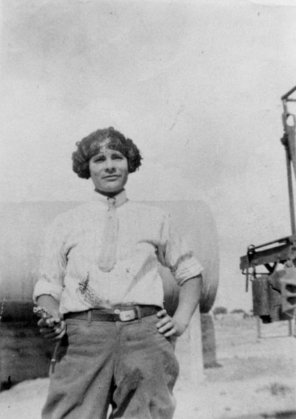 Grayscale photo of Maria Alatorre, a curly-haired person standing outside and wearing a men's shirt, pants, and tie.